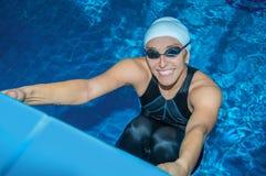 迷人的教练在水池游泳 免版税库存图片
