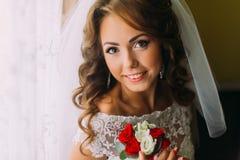 迷人的新娘特写镜头画象拿着与红色和白玫瑰的婚礼礼服的逗人喜爱的花束 库存照片