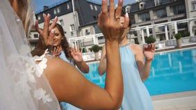迷人的新娘获得乐趣,当跳舞与她的女傧相在水池附近时 衣物夫妇日愉快的葡萄酒婚礼 股票视频