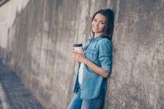 迷人的梦想的年轻深色的逗人喜爱的女孩在混凝土墙附近喝热的茶户外 她是困和轻松,在偶然jea 库存照片