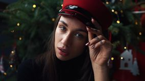 迷人的模型在红色冬天帽子摆在圣诞树前 股票录像