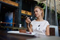 迷人的欧洲女性浏览wifi通过在早晨早餐期间的手机在咖啡馆酒吧,美好的妇女读书正文消息 图库摄影