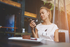 迷人的欧洲女性浏览wifi通过在早晨早餐期间的手机在咖啡馆酒吧 库存图片