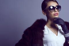 迷人的深色头发的模型画象在佩带白色女衬衫、黑貂外套和套豪华首饰的时髦的经典太阳镜的 免版税库存照片
