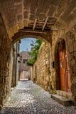 迷人的狭窄的街道在老镇罗得岛,希腊 免版税库存图片
