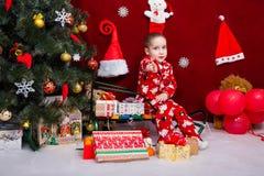 迷人的男孩坐雪橇在很多礼物旁边 免版税库存照片
