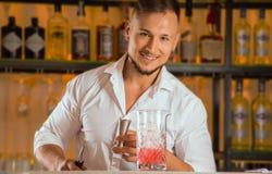 迷人的男服务员倾吐从瓶的酒精入火簸机 图库摄影