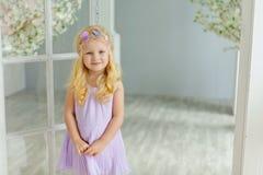 迷人的矮小的白肤金发的女孩微笑反对在光s的白色门 库存照片