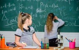 迷人的科学 o 女孩同学学习化学 显微镜试管化学反应 免版税库存照片