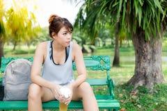 迷人的美丽的亚洲妇女坐长凳在美丽的公园 因为俏丽的女孩有,有吸引力的女孩感受尝试了,渴 免版税库存照片