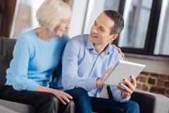 迷人的谈话人和他的资深的母亲,当使用片剂时 免版税库存图片