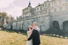 迷人的走在美丽的被破坏的巴洛克式的宫殿附近的新婚佳偶新娘和新郎 免版税图库摄影