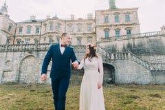迷人的走在美丽的被破坏的巴洛克式的宫殿附近的新婚佳偶新娘和新郎 免版税库存图片