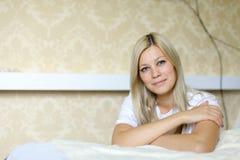 迷人的金发碧眼的女人为照相机微笑并且摆在,位于睡觉 库存图片