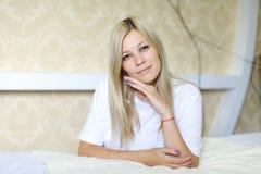 迷人的金发碧眼的女人为照相机微笑并且摆在,位于睡觉 免版税库存照片