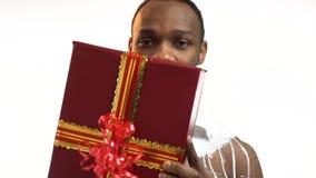 迷人的黑人寻找一件红色礼物并且微笑 股票录像