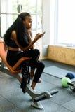 迷人的黑人少妇画象有发短信在她的在健身房的智能手机的豪华长的头发的 免版税库存图片
