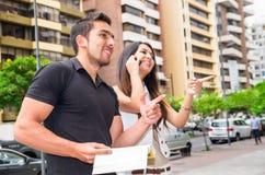 迷人的年轻夫妇常设外部在城市环境、藏品开放书和妇女里谈话在流动互动 免版税库存照片