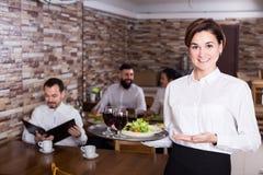 迷人的年轻女服务员问候顾客在桌上 免版税库存照片