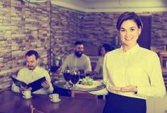迷人的年轻女服务员问候顾客在桌上 库存照片