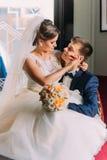 迷人的年轻新娘坐她一把豪华椅子的爱恋的新郎膝盖与发光的窗口作为背景 关闭 免版税库存照片