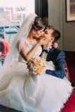 迷人的年轻新娘坐膝盖和亲吻她一把豪华椅子的爱恋的新郎与发光的窗口  库存图片