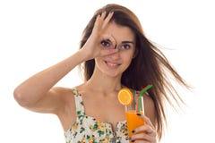 迷人的年轻深色的女孩在夏天穿衣与shoing花卉的样式好并且喝被隔绝的橙色鸡尾酒  免版税库存照片