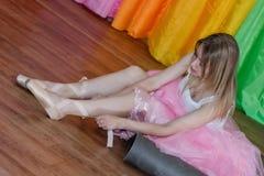 迷人的年轻芭蕾舞女演员投入有丝带的Pointe鞋子 库存照片
