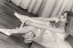 迷人的年轻芭蕾舞女演员投入有丝带的Pointe鞋子 库存图片
