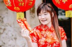 迷住美丽的亚洲女服cheongsam礼服的画象从她的家庭得到红色信封 俏丽的女孩显示红色信封 P 免版税库存图片