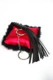 黑迷信鞭打的鞭子和legcuff在红色枕头 免版税库存照片