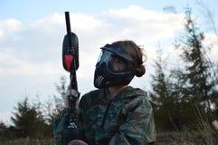 迷彩漆弹运动体育防护伪装制服和面具的球员女孩 免版税库存照片