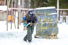 迷彩漆弹运动在冬天 凉快的人赛跑 免版税库存图片