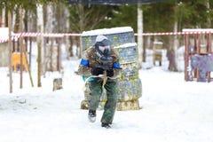 迷彩漆弹运动在冬天 奔跑的凉快的射击者 免版税库存照片