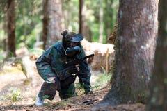 迷彩漆弹运动在树后的球员皮 免版税库存图片