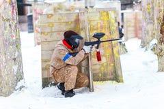迷彩漆弹运动比赛在冬天 在设防后的凉快的射击者 免版税库存照片