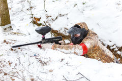 迷彩漆弹运动比赛在冬天 在设防后的凉快的射击者 免版税图库摄影