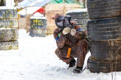 迷彩漆弹运动比赛在冬天 在设防后的凉快的射击者 图库摄影
