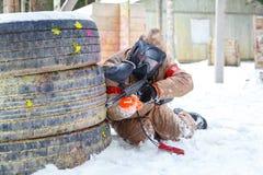 迷彩漆弹运动比赛在冬天 在设防后的凉快的射击者 库存图片