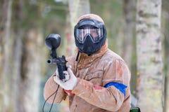 迷彩漆弹运动比赛在冬天 有标志的凉快的射击者 图库摄影