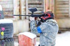 迷彩漆弹运动比赛在冬天 从标志的人射击 免版税库存图片