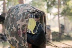 迷彩漆弹运动球员的特写 外形的人在一个防毒面具的伪装敞篷与在玻璃的一个黄色污点 图库摄影