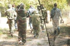 迷彩漆弹运动球员进入森林 免版税库存图片