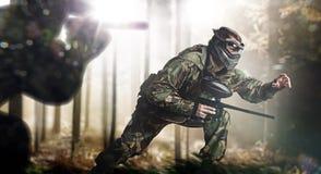 迷彩漆弹运动队在行动森林地点 免版税库存图片