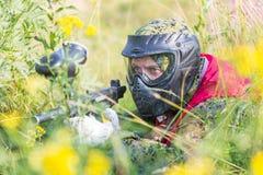 迷彩漆弹运动防护制服的体育使用与枪户外和偷偷地走在草的球员和面具 免版税库存照片