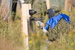 迷彩漆弹运动防护制服的体育使用和射击与枪的球员和面具户外 免版税库存图片