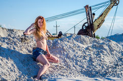 迷惑有长的美丽的头发在牛仔布短裤和比基尼泳装游泳衣的年轻人性感的女孩坐沙子山在的 库存图片