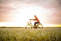 迷离无法认出的青年时期,乘驾自行车 春季,绿色gras 免版税库存照片