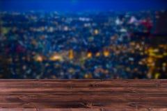 迷离有木桌的f夜城市 库存图片