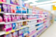 迷离有洗涤剂和软化剂产品的超级市场走道在架子背景 免版税库存照片